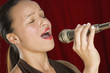 Woman singing into microphone with eyes closed