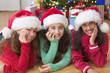 Portrait of three girls with Santa hats in front of Christmas tree