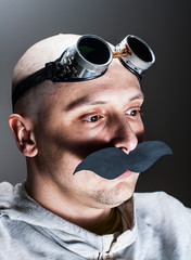Man wearing false moustache and goggles