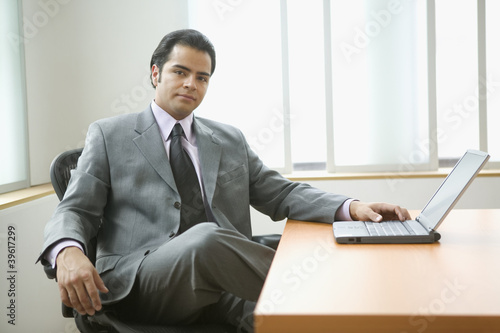 Portrait of businessman sitting at desk with laptop computer