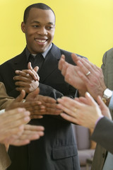 The hands of five people clapping and one man standing