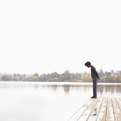 Man on dock looking into lake