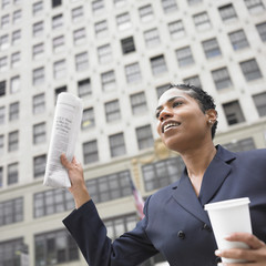 Business woman holding coffee and newspaper