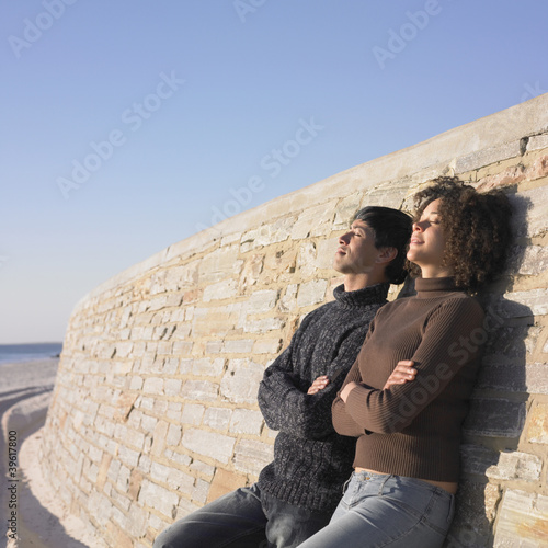 Young couple relaxing against a wall
