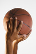 Close up of hand holding basketball in air