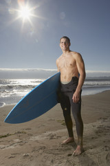 Portrait of man at beach with surf board