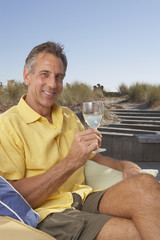 Portrait of man sitting holding wine glass at beach