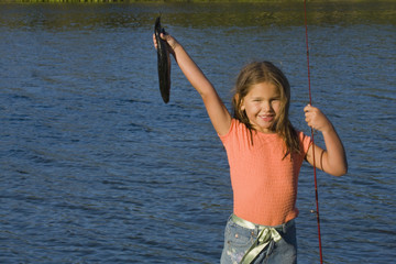 Portrait of girl holding up fish and fishing pole