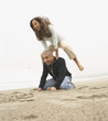 Couple playing leap frog at beach