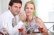 Couple sat at table enjoying intimate meal