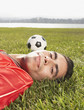 Portrait of man laying in grass with soccer ball