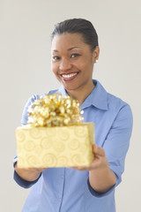 Woman smiling while offering a gift
