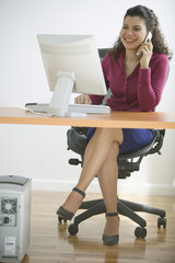 Businesswoman talking on phone while sitting at desk with computer