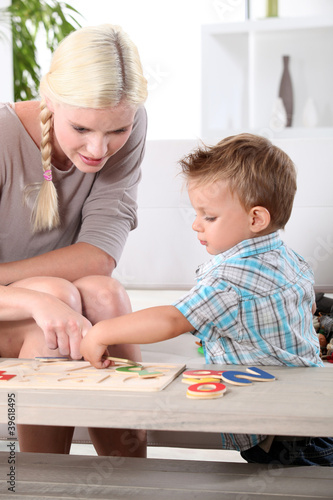 Mother and son doing a jigsaw puzzle Poster