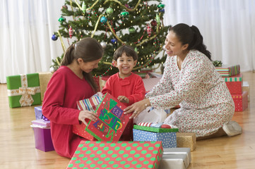 Family opening gifts on Christmas day in front of tree