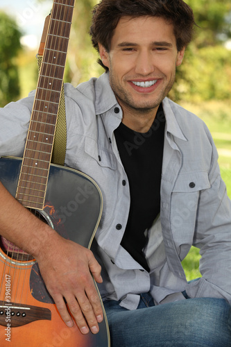 Young man sitting in a park with his guitar