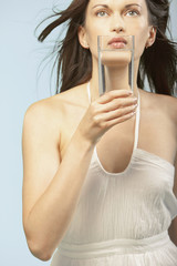 Portrait of woman holding glass of water to mouth