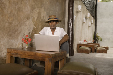 Man sitting in restaurant with laptop on table