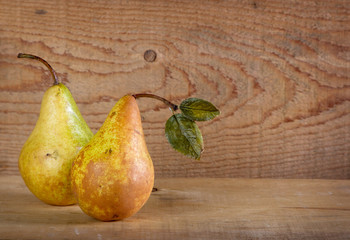 Two pears on a plank wooden background