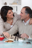 Loving couple playing chess together