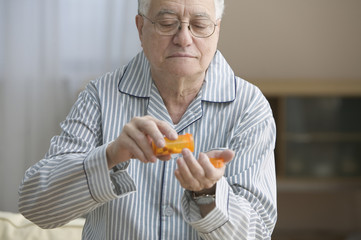 Older man shaking out pills into his hand
