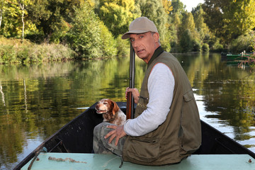 Hunter with a shotgun and dog on a boat
