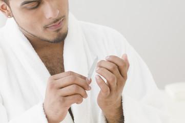Young man filing his nails
