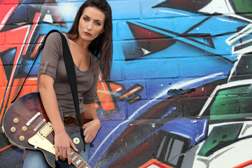 attractive brunet singer with guitar against graffiti wall