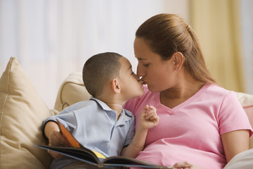 Mother and son kissing as they read together