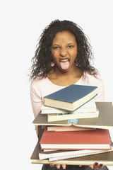 Teenage girl sticking her tongue out behind a pile of books