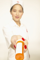 Female nurse holding out a jar of pills