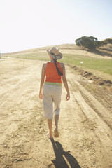 Young woman walking on a dirt road