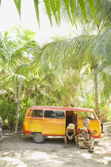 People sitting with van in tropical setting