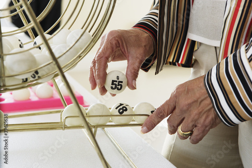 Elderly woman picking up a bingo ball