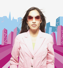 Woman posing for the camera in sunglasses against city background