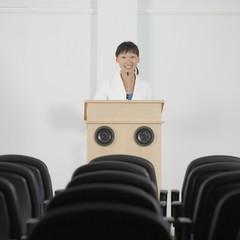 Businesswoman standing at podium