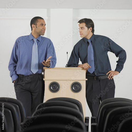 Two businessmen leaning on podium