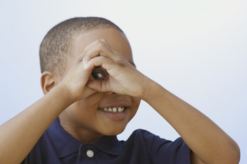 Close up of African American boy peeking through hands