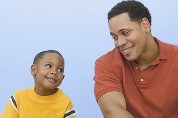 Father and young son smiling and looking at each other