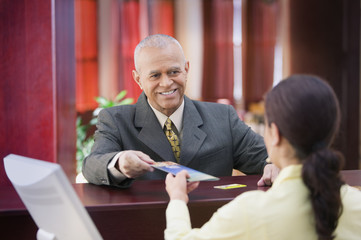 Businessman receiving brochure from a receptionist