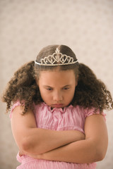 Young girl pouting with princess crown