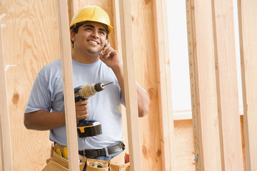 Construction worker talking on cell phone while holding drill