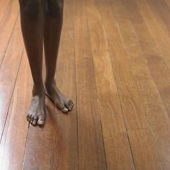 Young woman's bare feet on a hardwood floor