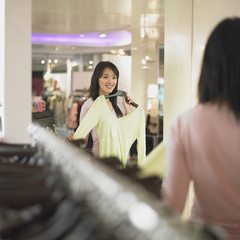 Young woman looking at new clothes in mirror