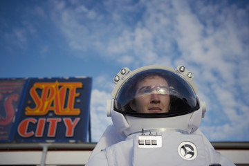 """Man in spacesuit leaving """"Space City"""""""