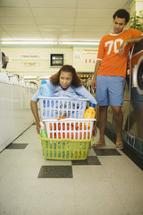Young woman trying to lift three laundry baskets