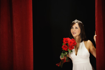 Woman wearing a tiara and holding a bouquet of roses