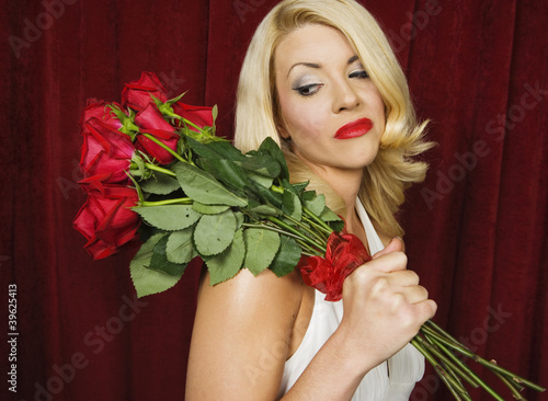 Young woman carrying a bouquet of roses over her shoulder