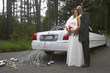 Newlyweds hugging by their car