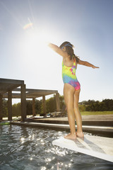 Little girl standing on the end of a diving board